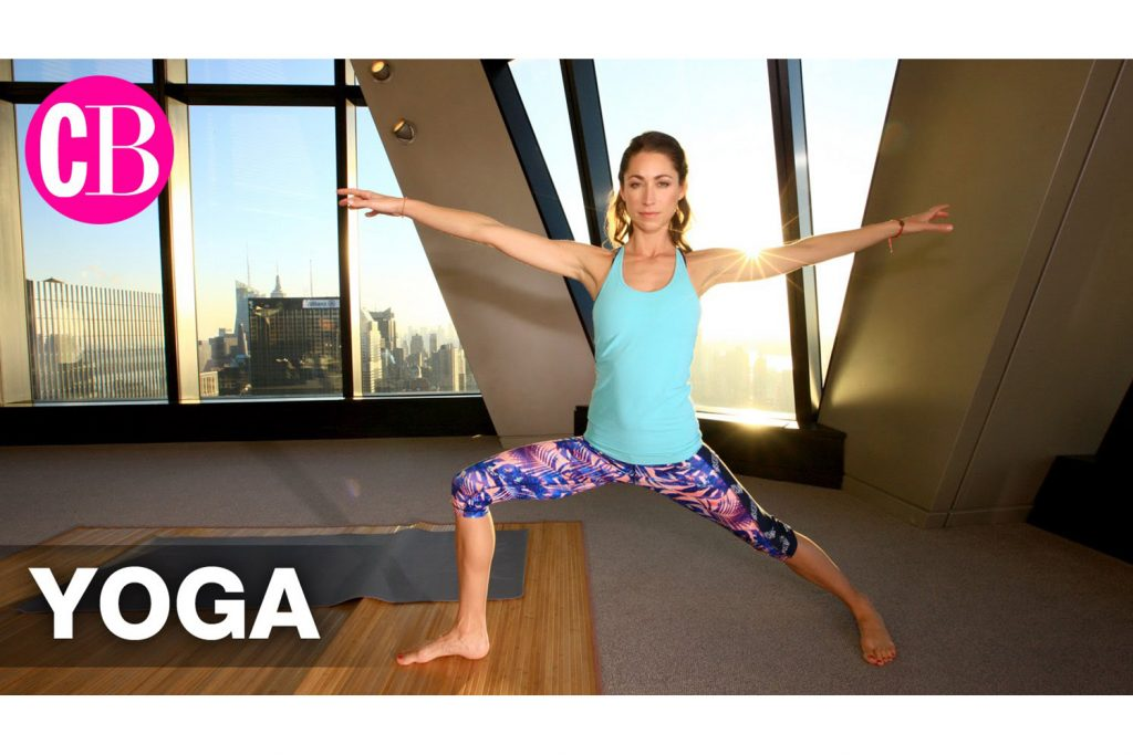 Woman in yoga clothes, in high rise studio space with large windows behind and golden hour light, in warrior 2 pose
