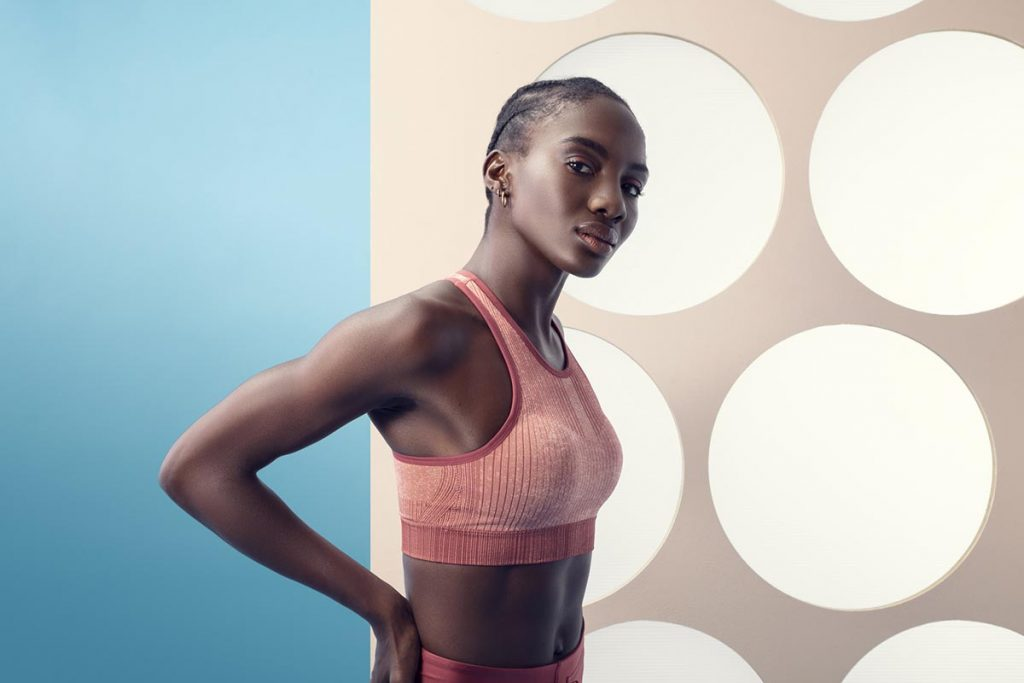 Ftiness model with sports bra. Backgorund blue and white with circles.