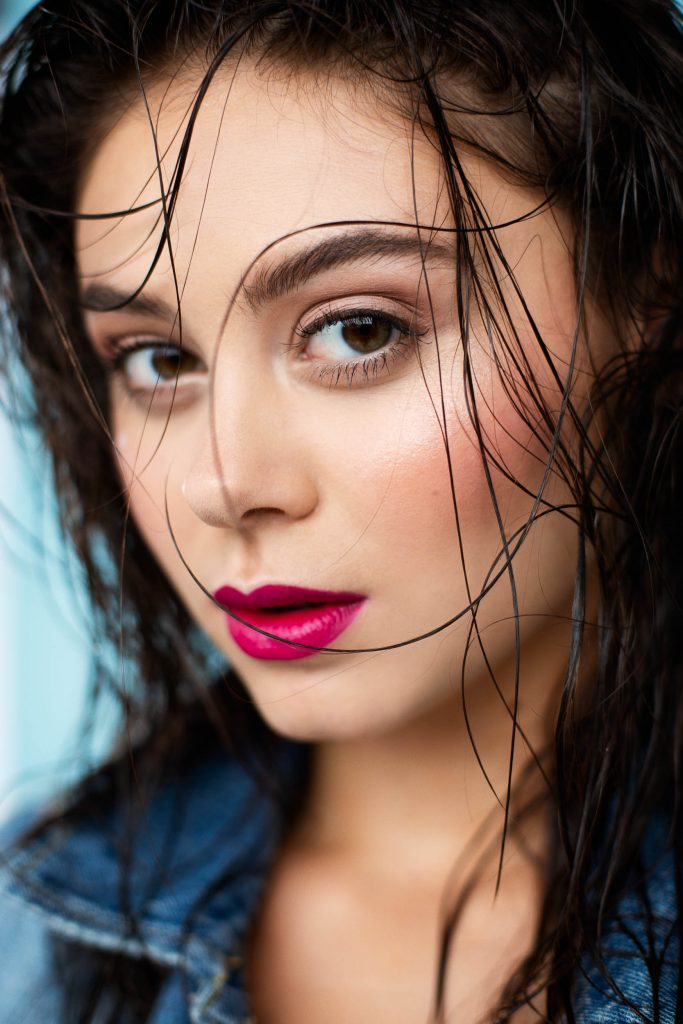 Sexy model with dark hair, magenta lipstick, perfect eyebrows, and wet hair