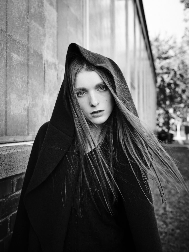 Model with red hair, very light skin, and brows in a hood, shot by Rodrigo Cid