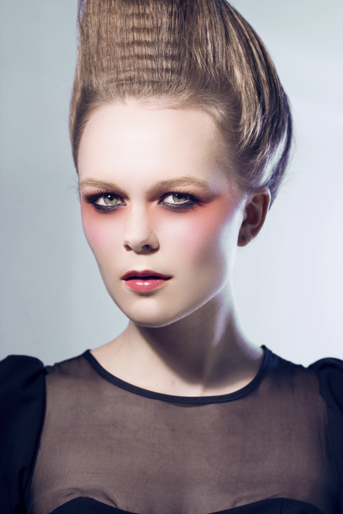 Model with alabaster skin skin and avant-gard makeup, looking to camera